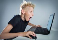 Jugendlicher an einem Computer Stockbild