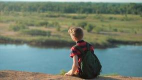 Jugendlicher in einem roten Hemd mit einem Rucksack auf seinem zurück, bei dem Sonnenuntergang, sitzend auf einem hohen Hügel und