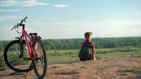 Jugendlicher in einem roten T-Shirt mit einem Rucksack auf seiner Rückseite, bei Sonnenuntergang, sitzend auf einem hohen Hügel u