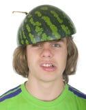 Jugendlicher in einer Schutzkappe von einer Wassermelone Stockfotos