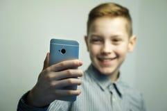Jugendlicher ernster Junge mit dem stilvollen Haarschnitt, der selfie auf Smartphone nimmt Stockfotos