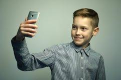Jugendlicher ernster Junge mit dem stilvollen Haarschnitt, der selfie auf Smartphone nimmt Stockbilder