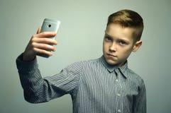 Jugendlicher ernster Junge mit dem stilvollen Haarschnitt, der selfie auf Smartphone nimmt Stockbild
