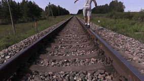 Jugendlicher geht über die Schiene weg hinaus stock video footage