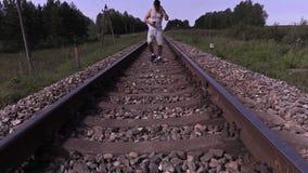 Jugendlicher hören auf Musik und das Gehen durch Schiene stock footage