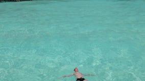 Jugendlicher hat einen Rest auf transparentem Wasser des Türkises Lizenzfreies Stockbild