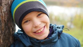 Jugendlicher im Herbstpark, der nahe einem Baum lächelnd und Kamera betrachtend steht Lizenzfreie Stockbilder