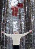Jugendlicher im Hut Santa Claus sammelt Geschenke in einem schneebedeckten Wald herein Lizenzfreie Stockfotos