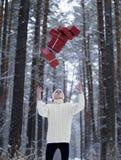 Jugendlicher im Hut Santa Claus sammelt Geschenke in einem schneebedeckten Wald herein Lizenzfreies Stockfoto