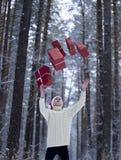 Jugendlicher im Hut Santa Claus sammelt Geschenke in einem schneebedeckten Wald herein Stockfotografie