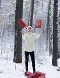 Jugendlicher im Hut Santa Claus sammelt Geschenke in einem schneebedeckten Wald herein Stockbilder
