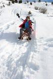 Jugendlicher Junge auf einem Schlitten im Schnee Stockfoto