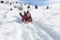 Jugendlicher Junge auf einem Schlitten im Schnee Stockbild