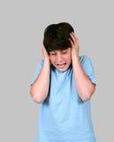 Jugendlicher Junge, der seinen Kopf anhält Stockfotografie