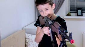 Jugendlicher Junge des Porträts, der zu Hause Kalaschnikow Riffle Gewehr der automatischen Waffe spielt und schießt stock footage