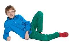 Jugendlicher Junge liegt auf dem weißen Hintergrund Lizenzfreie Stockbilder