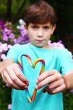 Jugendlicher Junge mit Regenbogensüßigkeitsstöcken Stockbilder