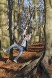 Jugendlicher kaukasischer Junge, der von einem Seil-Schwingen hängt lizenzfreies stockfoto
