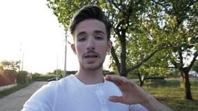 Jugendlicher männliches vlogger Gehen und Schreibschriften durch Haar, während notierende Videoaußenseite in der Natur - stock video