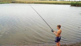 Jugendlicher mit Angelrute auf dem Ufer des Sees stock video