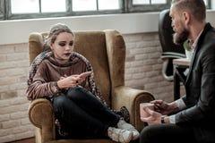 Jugendlicher mit dem dunklen Make-up, das dem Psychologen über Auseinanderbrechen spricht lizenzfreie stockfotografie