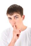 Jugendlicher mit dem Finger auf seinen Lippen Stockfoto