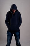 Jugendlicher mit dem Hoodie, der unten gegen eine schmutzige graue Wand schaut Stockfotos