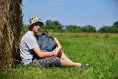 Jugendlicher mit dem Rucksack, der nahe bei Stapel Stroh sitzt stockbild