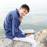 Jugendlicher mit einem Buch Stockbild