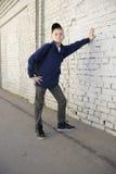 Jugendlicher mit einem durchdachten Blick Hintergrundbacksteinmauer Lizenzfreies Stockbild