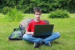 Jugendlicher mit einem Laptop im Park Stockfotos