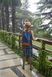 Jugendlicher mit einem Rucksack kostet unter einem Sommerregen Stockfotografie