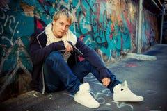 Jugendlicher mit einer Pistole, die nahe Graffitiwand sitzt Stockfotografie