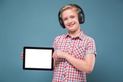 Jugendlicher mit Kopfhörern zeigt Smartphoneanzeige, Foto mit Raum für Text Lizenzfreie Stockfotos