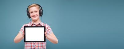 Jugendlicher mit Kopfhörern zeigt Smartphoneanzeige, Foto mit Raum für Text Lizenzfreie Stockbilder