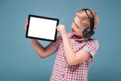 Jugendlicher mit Kopfhörern zeigt Tablettenanzeige, Foto mit Raum für Text Stockfotografie