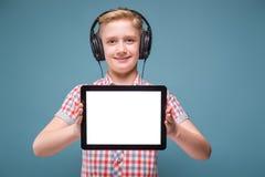 Jugendlicher mit Kopfhörern zeigt Tablettenanzeige, Foto mit Raum für Text Stockfoto