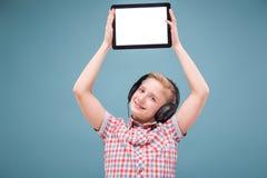 Jugendlicher mit Kopfhörern zeigt Tablettenanzeige, Foto mit Raum für Text Lizenzfreie Stockfotos