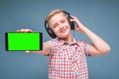 Jugendlicher mit Kopfhörershows Smartphoneanzeige Stockfotos
