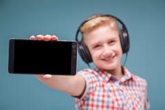 Jugendlicher mit Kopfhörershows Smartphoneanzeige Lizenzfreie Stockbilder