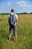 Jugendlicher mit Rucksack steht mit seiner Rückseite auf Wiese stockfotos