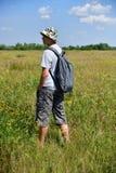 Jugendlicher mit Rucksack steht mit seiner Rückseite auf Wiese lizenzfreie stockfotografie