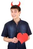 Jugendlicher mit Teufel-Hörnern und Herzen Stockbild