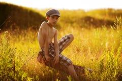 Jugendlicher sitzt auf Treibholz Stockbild