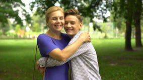 Jugendlicher Sohn, der seine geliebte Mutter, freundliche Verhältnisse, Verständnis küsst stock footage