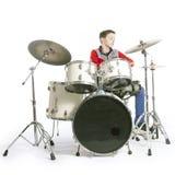 Jugendlicher spielt Trommeln im Studio mit weißem Hintergrund Stockfotografie