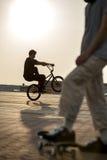 Jugendlicher springen auf Fahrrad draußen, Junge auf Skateboard, städtisches styl Stockbilder