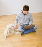 Jugendlicher und Laptop-Computer und Hund Lizenzfreies Stockfoto