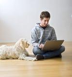Jugendlicher und Laptop-Computer und Hund Stockfotografie