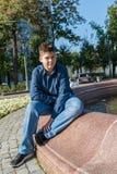Jugendlicher von 14 Jahren sitzt nahe Brunnen lizenzfreie stockfotografie